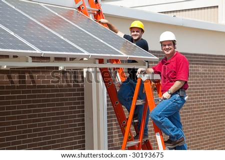 Happy electricians employed to install energy efficient solar panels in the new green economy. - stock photo