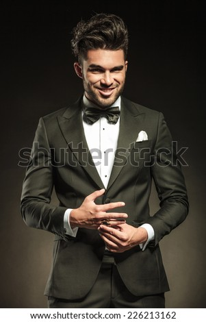 Happy elegant business man smiling for the camera while fixing his ring. - stock photo