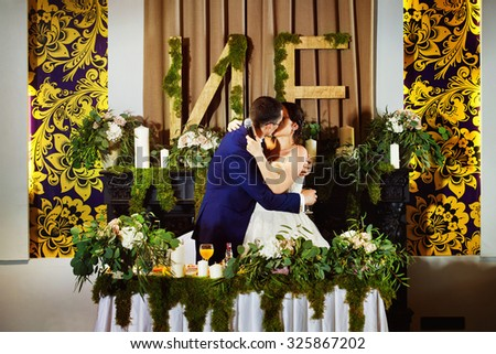 Happy elegant groom is kissing beautiful wife at decorated table stylish background in restaurant.