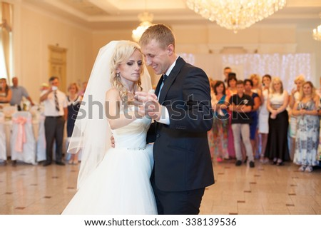 happy elegant married couple performing first dance in a restaurant, celebrating wedding - stock photo
