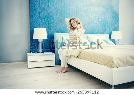Happy elegant woman having a rest in her bedroom. Home interior, furniture. Lifestyle. - stock photo