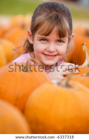 Happy elementary girl surrounded by bright orange pumpkins.