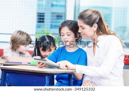 Happy elementary students with teacher. - stock photo