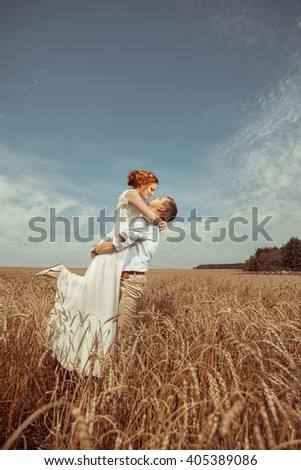 Happy embracing couple on the wheat field background. - stock photo