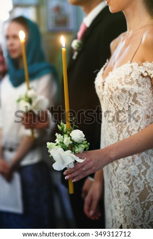 Happy emotional beautiful bride and cheerful groom with candles in church ceremony - stock photo