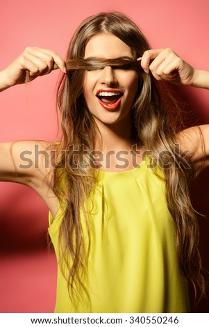 Happy emotional young woman in bright yellow dress laughing sincerely. Beauty, fashion concept. Hair, healthy hair.   - stock photo