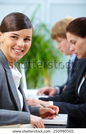 Happy employer looking at camera in working environment