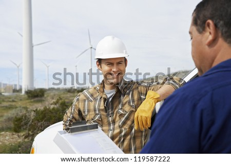 Happy engineer at wind farm with foreman in foreground with clipboard - stock photo