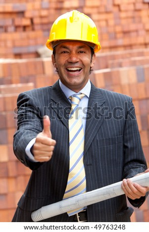 Happy engineer holding a model in a construction with his thumb up