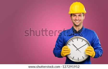 Happy Engineer Holding Wall Clock On Coloured Background - stock photo