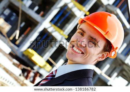 Happy engineer in helmet while building - stock photo
