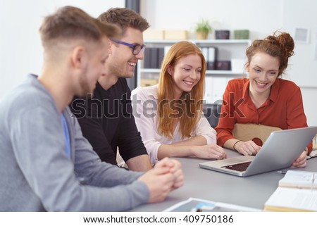 Happy enthusiastic diverse young business team sitting at a table grouped around a laptop computer smiling and laughing as they work