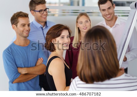 Happy enthusiastic young businesswoman leading a meeting of co-workers as they stand grouped around a flip chart brainstorming and discussing ideas