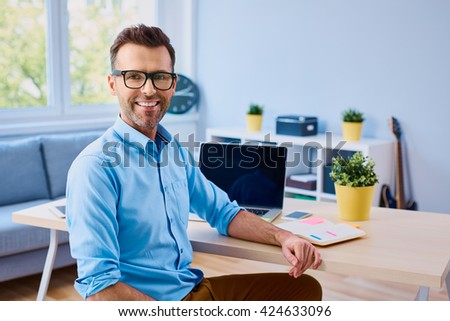 Happy entrepneur sitting by desk at home office, working on laptop - stock photo