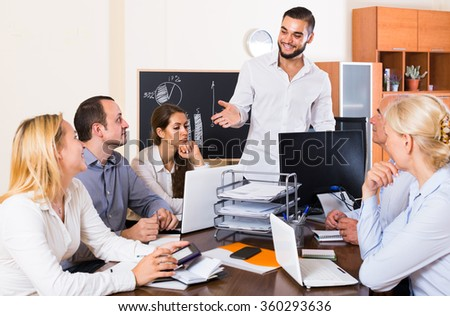 happy european colleagues discussing price development at office - stock photo
