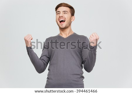 Happy excite young man in grey pullover screaming and celebrating his succcess over white background - stock photo