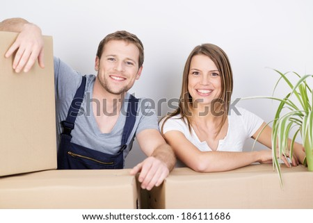 Happy excited attractive young couple moving to a new home looking over a pile of cardboard boxes at the camera with joyful smiles of anticipation - stock photo