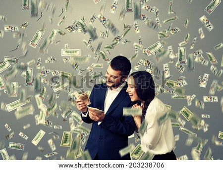 happy excited couple with money standing under dollar's rain - stock photo