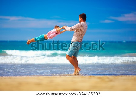 happy excited father and son having fun on summer beach, enjoy life - stock photo