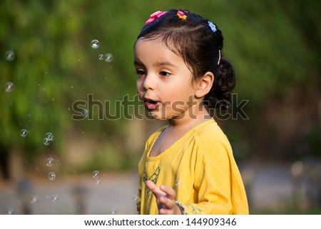 happy excited little girl playing with water bubbles - stock photo