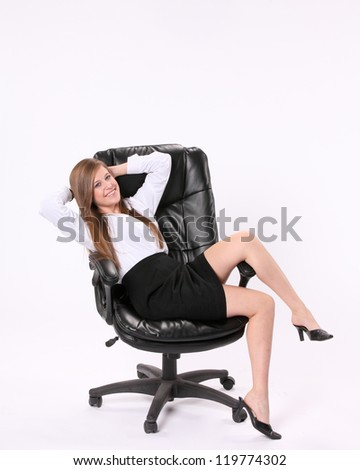 Happy excited secretary sitting cross ways in a swivel chair with her hands behind her head against a white background. - stock photo