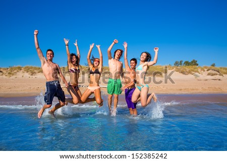 Happy excited teen boys and girls group jumping at the beach splashing water - stock photo