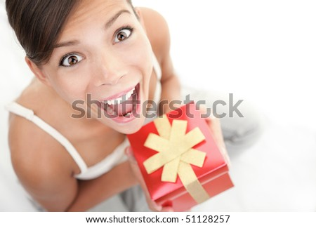 Happy excited woman holding gift / present. Cute surprised mixed Asian Chinese / Caucasian female model.