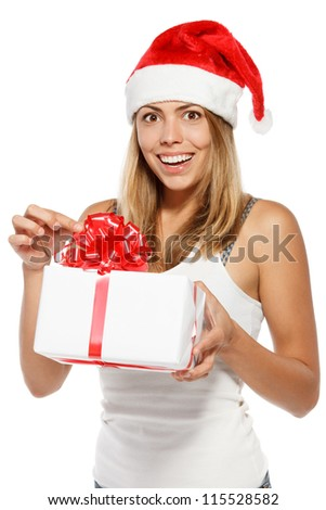 Happy excited woman in Santa hat unwrapping a Xmas gift, isolated on white background - stock photo