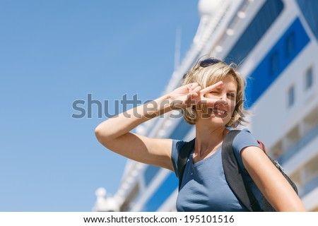 Happy excited woman tourist dancing of joy, in front of big cruise liner, summer day - stock photo
