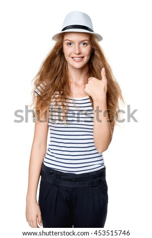 Happy excited woman with straw hat smiling at camera gesturing thumb up - stock photo