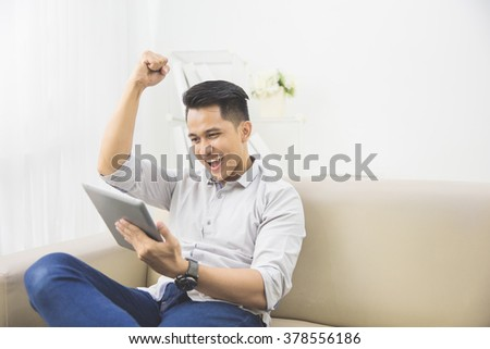 happy excited young man with tablet raised his arm at home sitting on a couch