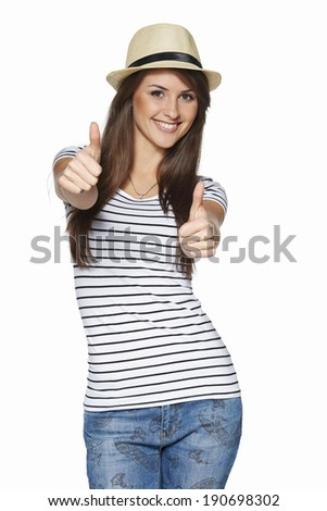 Happy excited young woman in striped tshirt and straw hat giving thumbs up, over white background - stock photo