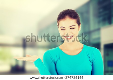 Happy , excited young woman presenting copy space on her palm. - stock photo