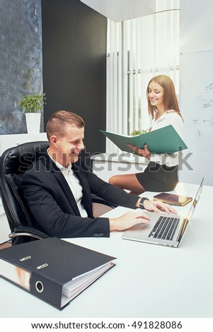 Happy executive or secretary giving documents to a businessman in a desktop at office