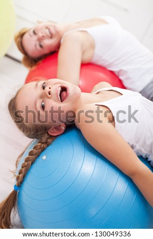 Happy exercising - little girl and her mother doing gymnastic - stock photo