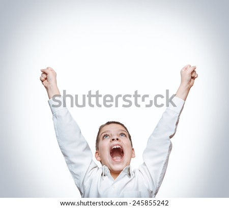 Happy exited screaming boy, hands up. - stock photo