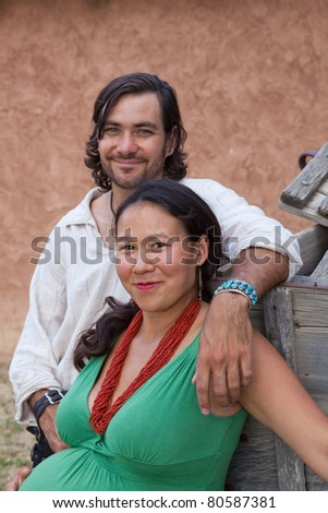 Happy expecting multicultural couple. Shallow DOF, focus is on woman's face. - stock photo