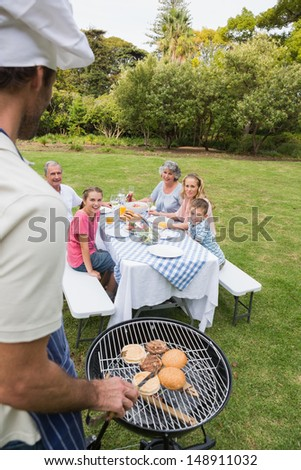 Happy extended family having a barbecue being cooked by father in chefs hat outside in the sun - stock photo