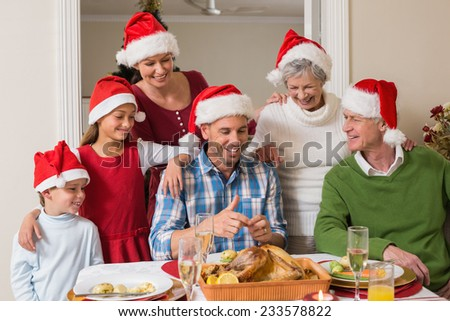 Happy extended family in santa hat at christmas dinner at home in the living room - stock photo