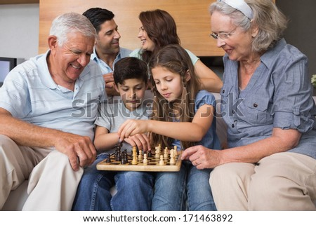 Happy extended family playing chess on sofa in the living room at home