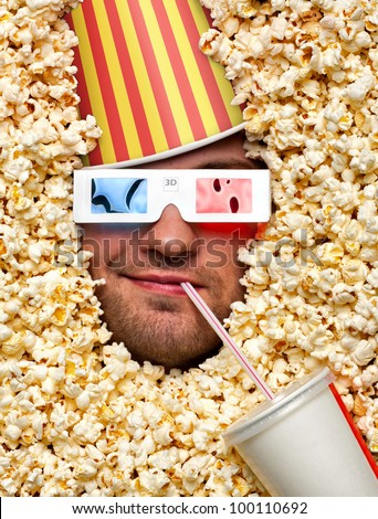 Happy face in popcorn with bucket on head watching 3D movie and drinking soda