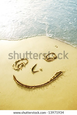 happy face in sand - stock photo