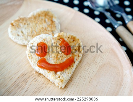 Happy face on the bread cutting in shape of heart. Concept about love and happiness         - stock photo