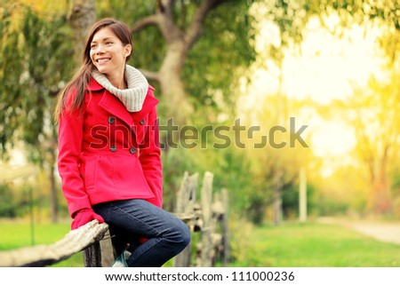 Happy fall woman sitting on countryside fence smiling joyful in autumn forest. Young beautiful multicultural Caucasian / Asian woman model outdoors - stock photo