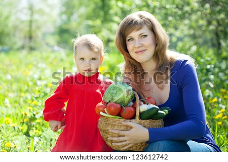 Happy  famile with vegetables harvest in garden