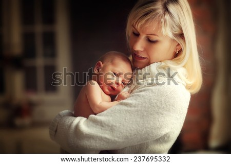 Happy family: a close up portrait of a beautiful young blonde woman in white clothes holding her cute newborn baby in a white suit. - stock photo