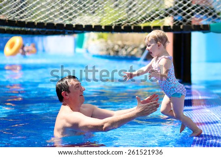 Happy family, active father with little child, adorable toddler girl, having fun together in outdoors swimming pool in waterpark during sunny summer sea vacation in tropical resort. Focus on kid - stock photo