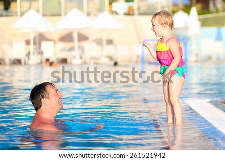 Happy family, active father with little child, adorable toddler girl, having fun together in outdoors jumping and swimming pool in aquapark during sunny summer sea vacation in tropical resort. - stock photo