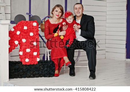 Happy family and daughter sitting on a chair near decor, background white and violet wooden room - stock photo