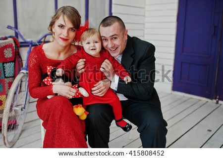 Happy family and daughter sitting on a chair near rustic vintage bicycle with decor, background white and violet wooden room - stock photo